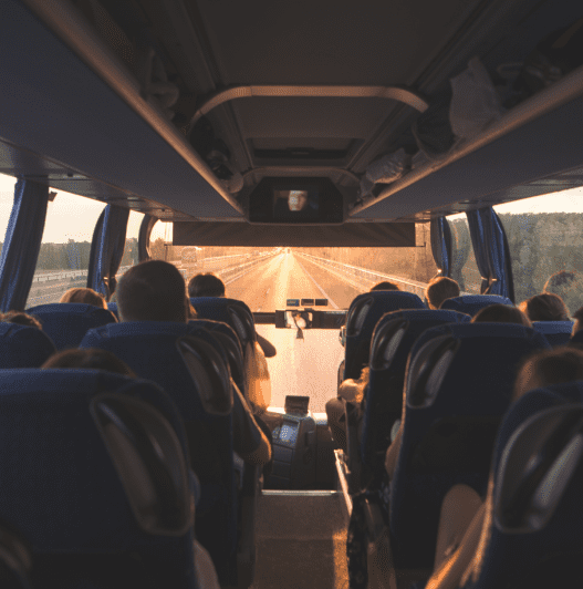 Bus with people going on the road in the evening at sunset. Photo interior of the bus. Background