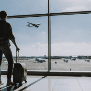 Man is watching plane flying from airport 300x300