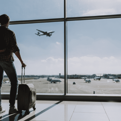 Man is watching plane flying from airport