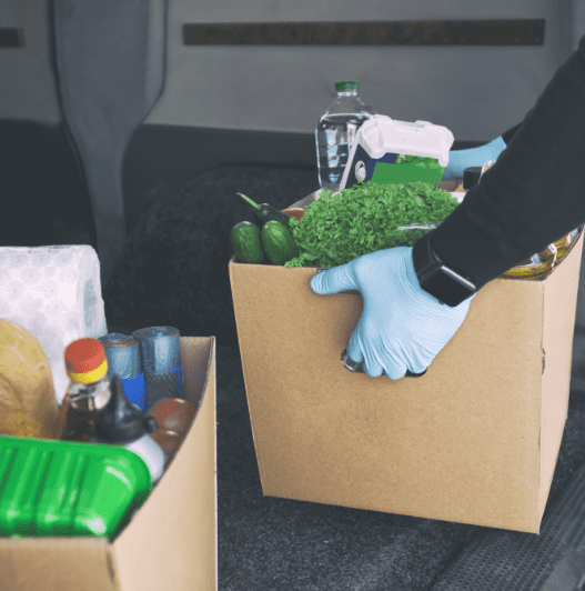 The courier takes the cardboard eco box with products from grocery shop out from the van