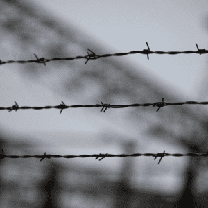 barbed wire with the blurred background of a refugee camp 300x300