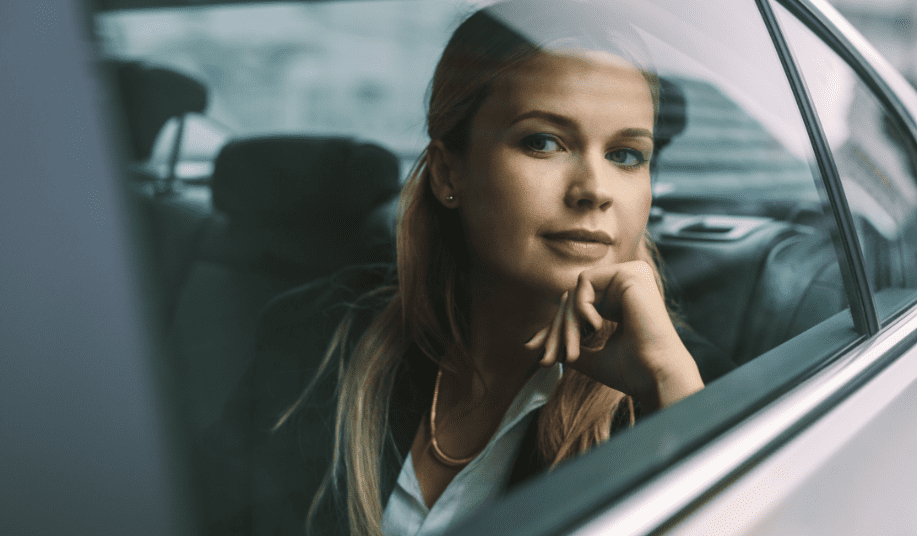 Female executive travelling by a car 1